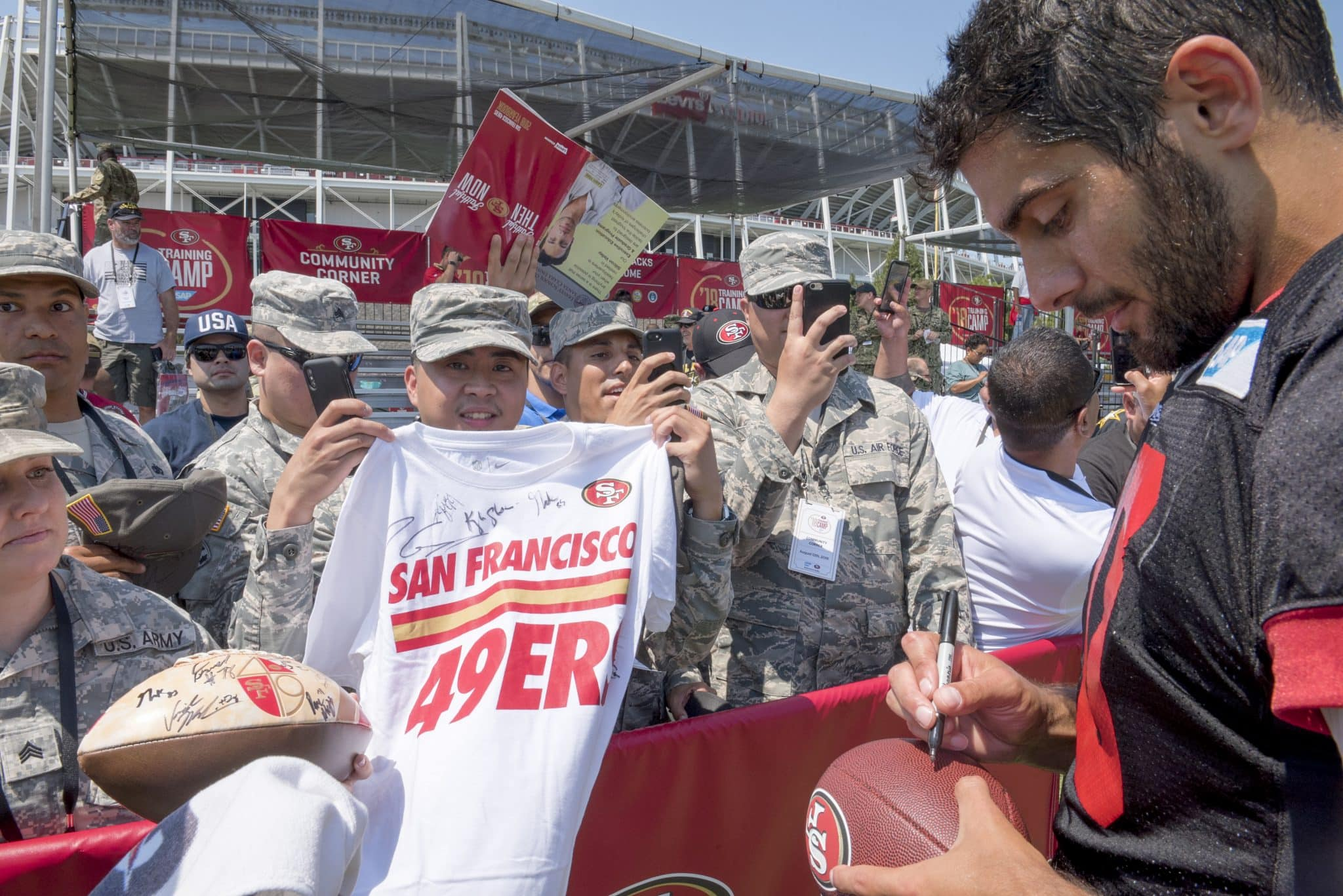 Jimmy Garoppolo, a 49ers quarterback, signs a football for a fan at the SAP Performance Facility, Santa Clara, Calif., Aug. 12, 2018. The 49ers organization invited military members from the local area to observe their training camp during a military appreciation day. (U.S. Air Force photo by Lan Kim)